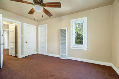 Back bedroom with carpeting, ceiling fan and a walk-in closet.