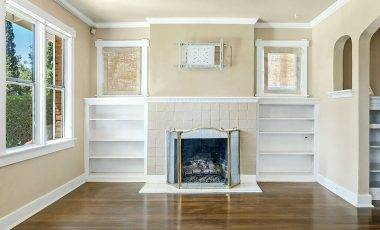 Wood-burning fireplace flanked by built-in display shelves.