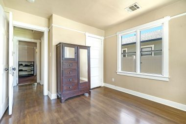 Alternate view of front bedroom, looking down the hallway to the bathroom and other two bedrooms.