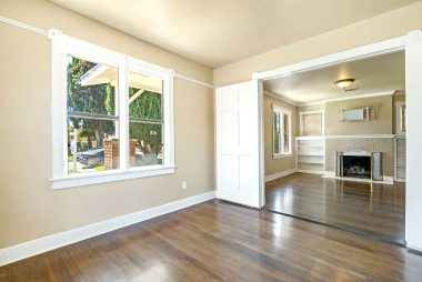 Front bedroom with double doors open with view into living room.