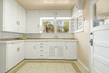 Light and bright kitchen with tile flooring and tile counter tops.