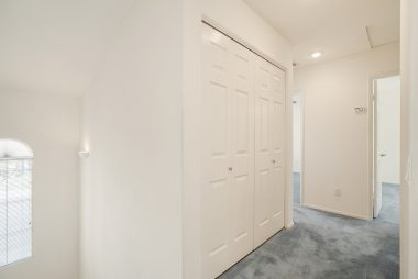 Hallway with laundry closet leading to the secondary bedrooms and bathroom.