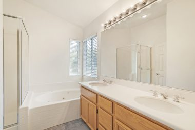 Master bathroom with dual sinks, spa tub, and separate shower.