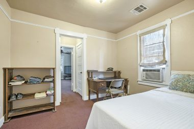 Middle bedroom with carpeting and a walk-in cedar closet.