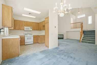 View from formal dining area into the beautiful kitchen with dishwasher, gas stove, built-in microwave, and new flooring.