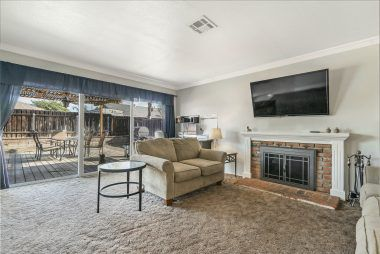 Spacious living room with fireplace and large slider overlooking the backyard.