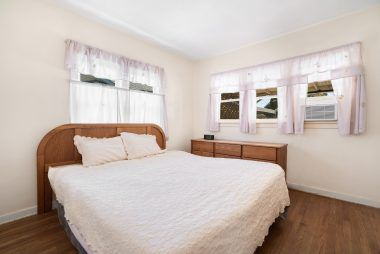 Back bedroom with hardwood flooring. This is a king size bed.