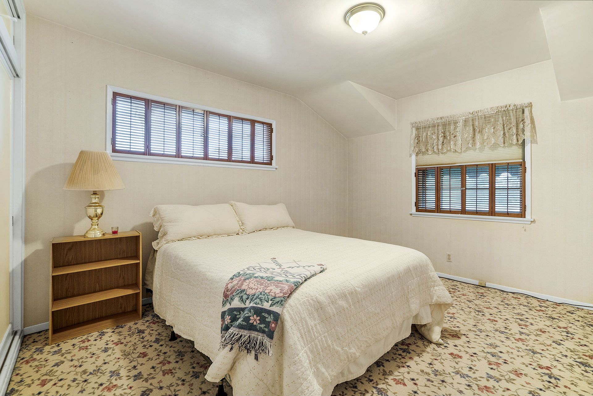 Large front bedroom with huge closet and original wood window shutters.