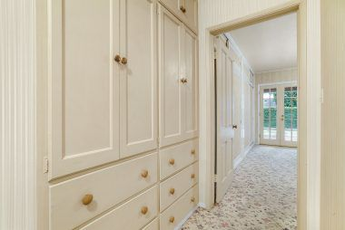 Extra large linen closet and cabinets in hallway leading to the master bedroom suite.