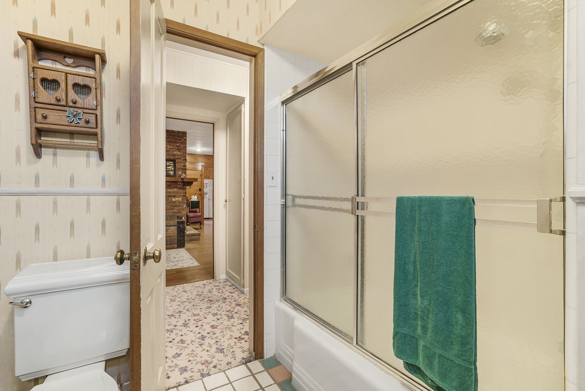 Alternate view of hallway bathroom with shower in tub.