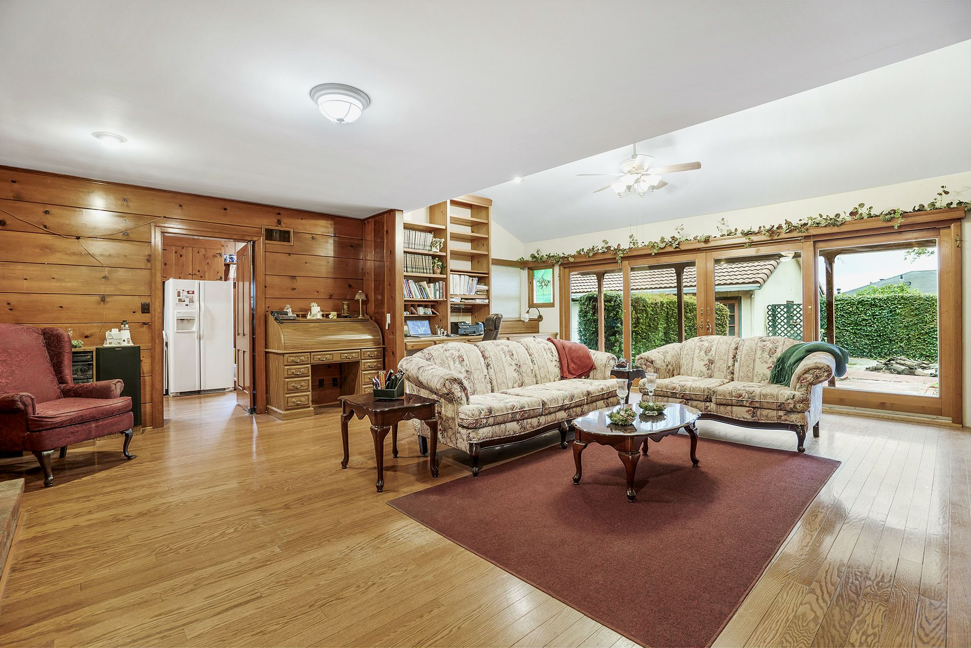Gigantic family room with media niche, lots of bookshelves, built-in desk, floor to ceiling windows and slider overlooking the backyard, and a cozy fireplace.