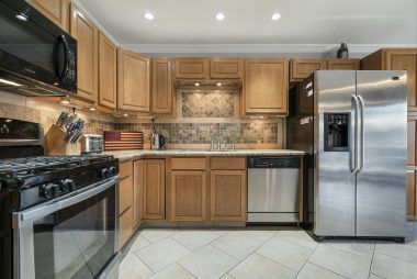 Remodeled kitchen with granite counters, tile floor, stainless steel appliances, including gas stove, microwave, and dishwasher.