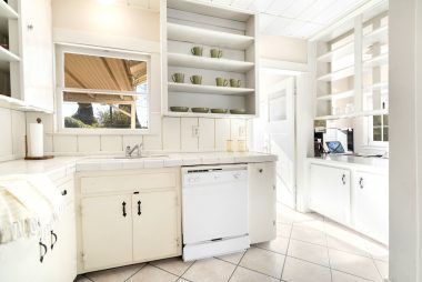 Open-cabinet kitchen with dishwasher, tile floor, and shelves separating the breakfast nook/office.