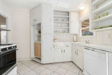 Open-cabinet kitchen with dishwasher, gas stove, and cute corner cubby for recipe books, etc.