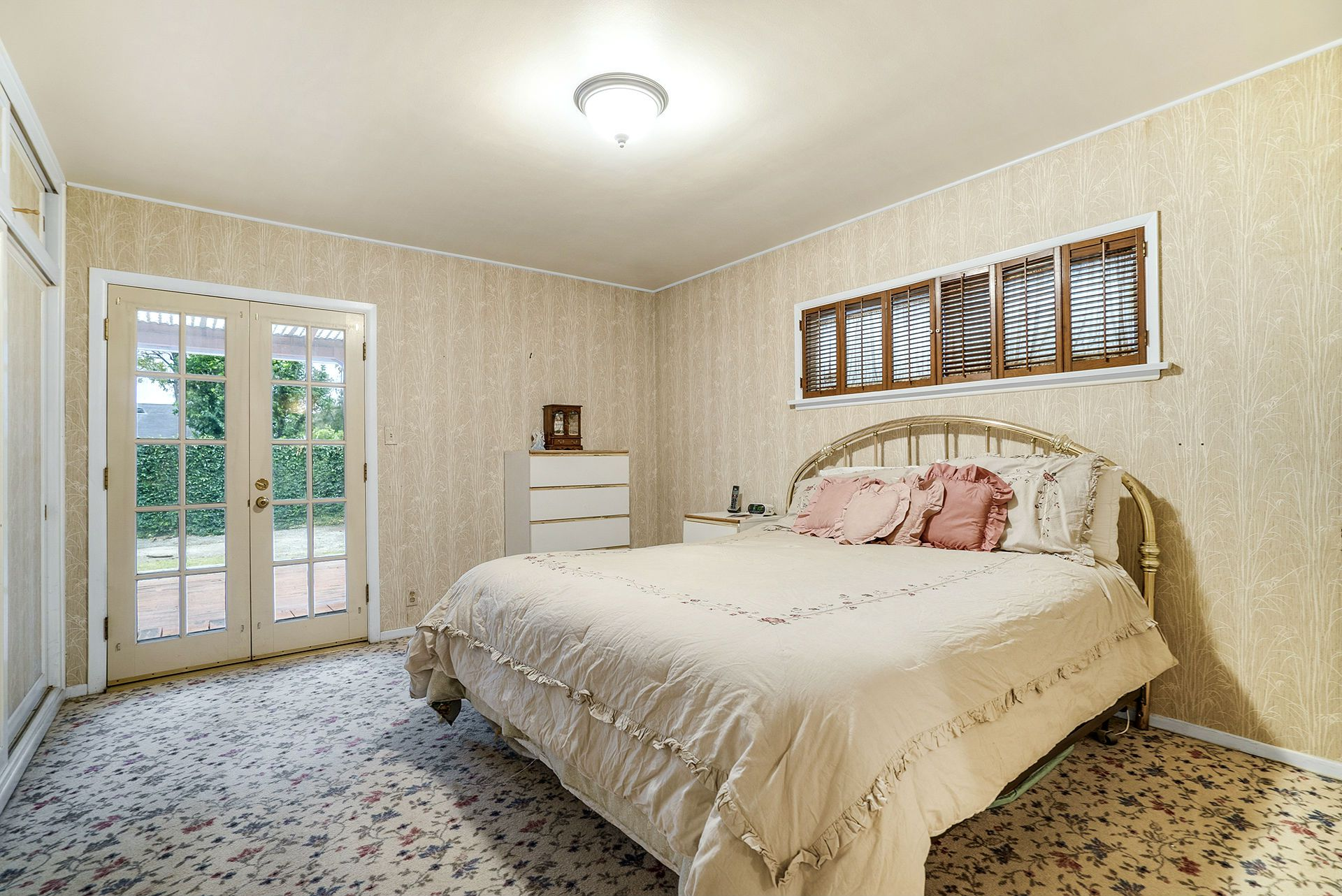 Master bedroom suite with French doors overlooking the deck and backyard.