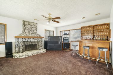 Wide-screen TV and entertainment center, as well as bar and shelving are included.