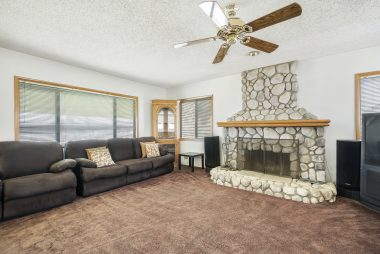 Spacious living room with custom gas and wood-burning river rock fireplace.