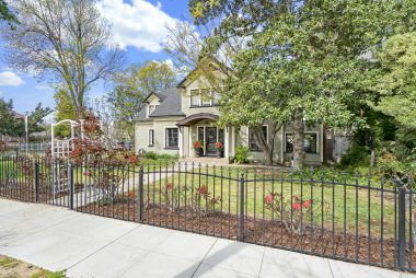 Brockton Avenue view with black wrought iron fence around entire front yard.