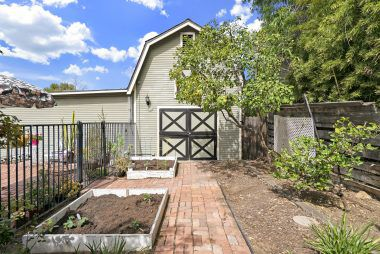 Backyard garden area with view of 2-story barn which is ideal for storage or game room.