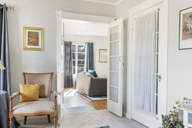 Open French doors welcome you to the family room, with the French door to the right leading to the 2nd story stairwell.