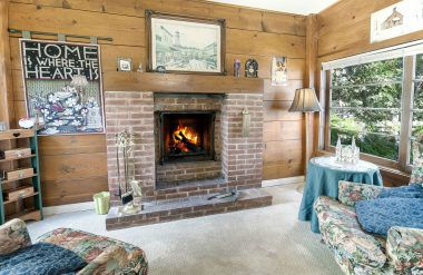 Step-down sitting room with fireplace and natural light.