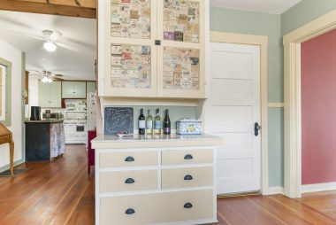 View from informal dining nook back into kitchen. Doorway leads to the back stairwell to 2nd floor, and note the old wine labels decoupaged onto the cabinet doors.