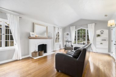 Large living room with original hardwood floors, fireplace, and built-in shelving.