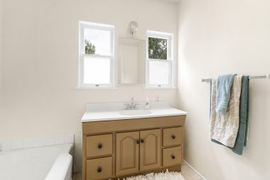 Light and bright bathroom with shower in tub.