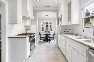Alternate view of kitchen with gas stove, looking into the bright breakfast nook.