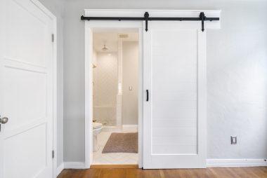 Sliding barn door leading to remodeled master bathroom.