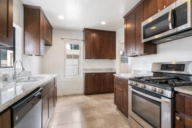 Remodeled kitchen with stainless steel appliances (except refrigerator), including built-in microwave, recessed lighting, and garden window.