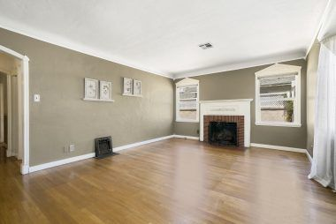 Living room with hardwood floors, two toned paint, decorative vintage floor vents, and gas & wood-burning fireplace.