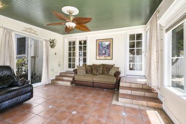 Step-down family room (sun room) with Saltillo tile and ceiling fan.