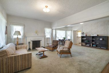 Spacious living room/dining room combo with wood-burning fireplace and hardwood floors.