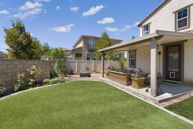Backyard is large enough for a pool, if desired. Yard is composed of synthetic grass with cement border, and enclosed with block wall and vinyl fencing.