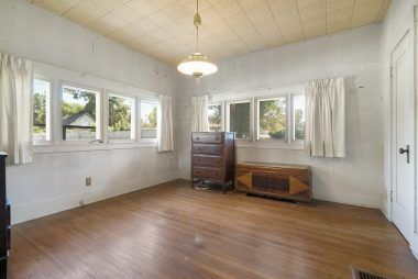 Back bedroom with hardwood floors and lots of windows.
