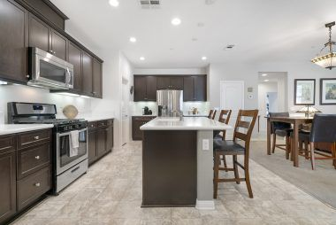 Stainless appliances in gourmet kitchen with giant breakfast island, granite counters, and recessed lighting.