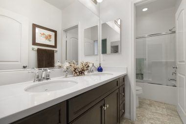 Hallway bathroom with dual sinks and shower-in-tub.
