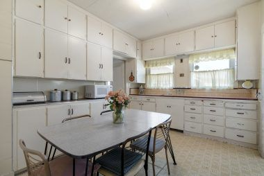 Spacious vintage kitchen with high ceiling and lots of cabinetry.