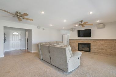 Larger view of the living room with recessed lighting, ceiling fans, and view to the front door entry.