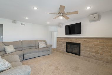 The living room swallows up a sectional sofa. Look at this amazing fireplace mantel too!