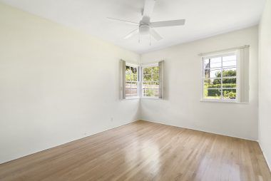 Bedroom #2 (overlooking back yard) with ceiling fan and original hardwood floors which were recently refinished.