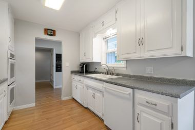 Light and bright kitchen with lots of counter space and cabinetry, including dishwasher and double oven.