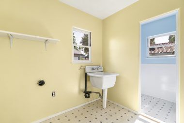 Separate indoor laundry room with utility sink.
