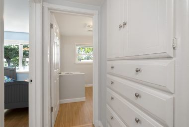 Hallway linen closet with view into front bedroom on left, and hallway bath straight ahead.