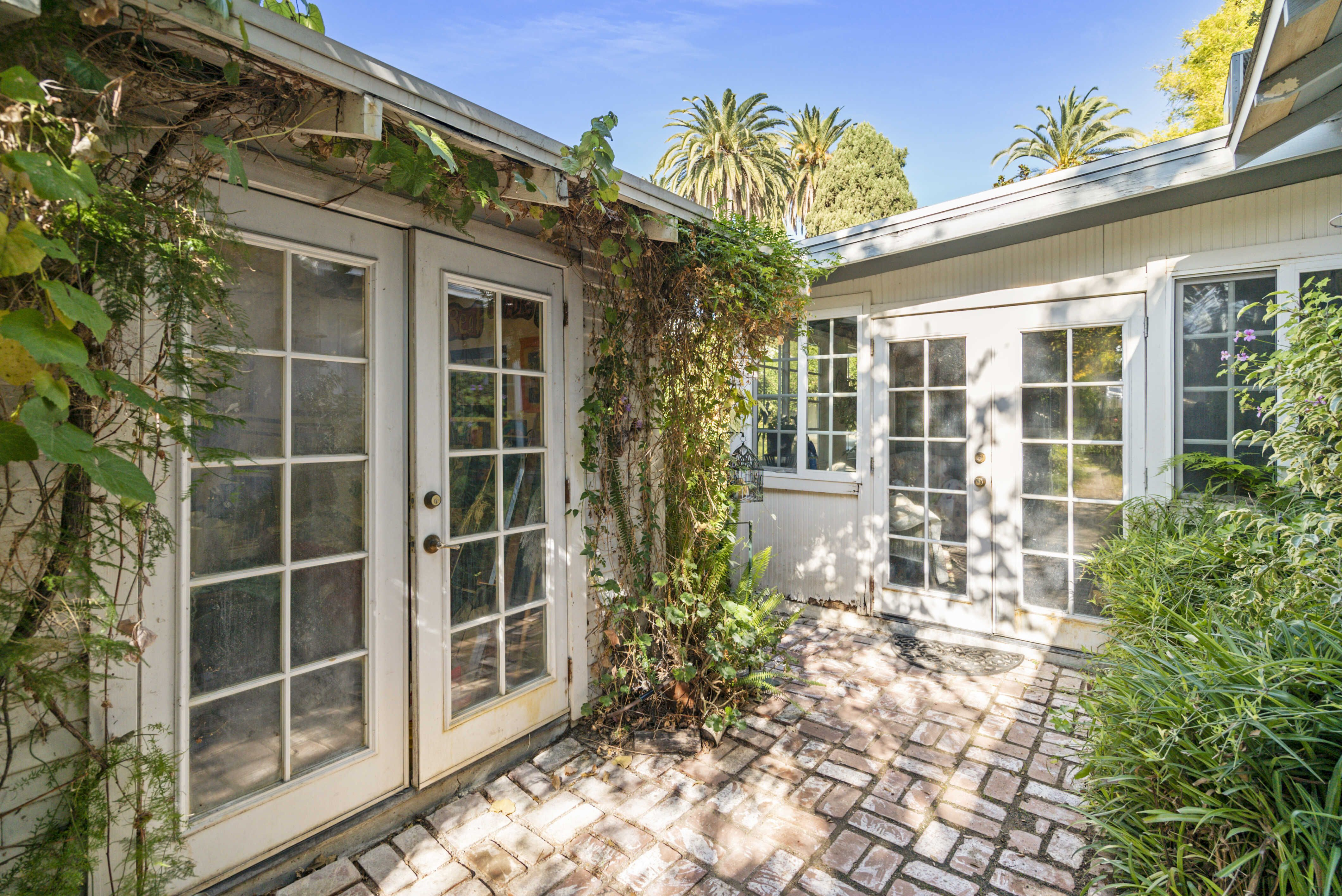 Set of French doors to the right lead to the sun room, and set of doors to the left lead to the converted garage which is now an art studio.