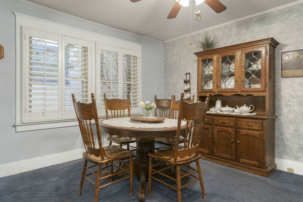 Formal dining area with ceiling fan and plantation shutters over double pane windows.