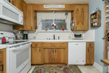Kitchen was updated about 20 years ago with tile counters. There's a newer stove, built-in microwave, dishwasher, and refrigerator (included).