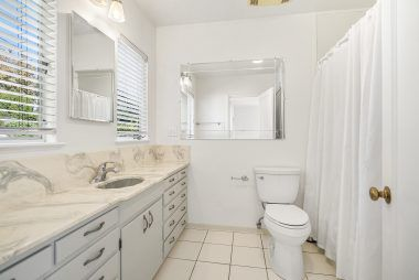 Private master bathroom #1 with shower in tub, large vanity, and tile flooring.