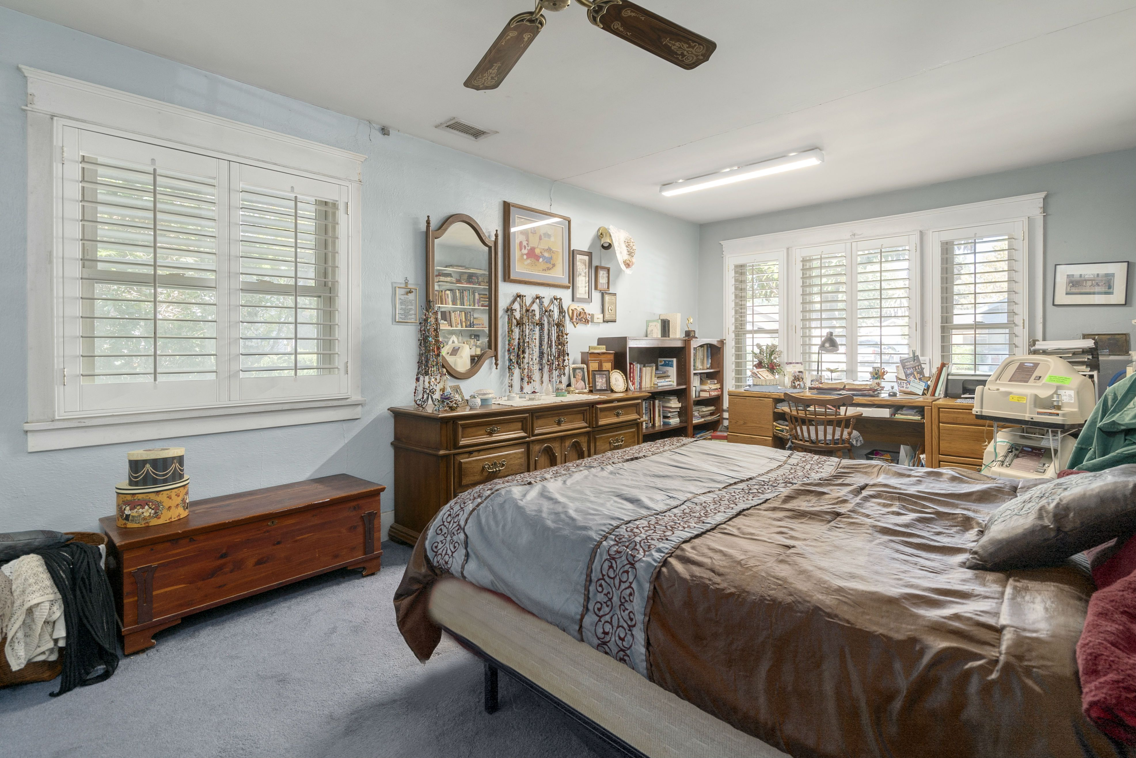 Front bedroom (largest of all 3) with ceiling fan, extra space toward the front window due to the permitted enclosure of the original front porch back in the 1970s.
